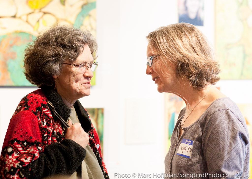 Artist Jacqui Beck talks with a visitor at the opening of Gender Personal at the Kirkland Arts Center.